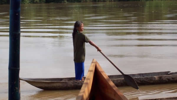 A woman travels down the river in a canoe.